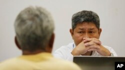An investigator of Thailand's Department of Special Investigation interrogates a key suspect in a human trafficking ring, Samruay Chatkrod, left, in Bangkok, Thailand, Wednesday, July 1, 2015.