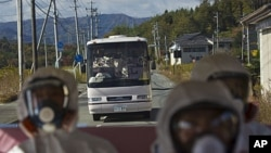 Japanese officials wearing protective suits and masks ride in the back of a bus while a second bus carrying officials and Japanese journalists follow as they drive through the contaminated exclusion zone on their way to the crippled Fukushima Dai-ichi nuc