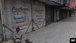 A Pakistani street vwndor sits next to a row of shuttered shops in a Karachi market after a week long period of violence in the city, March 31 2012.