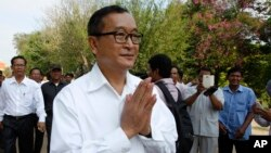 Cambodian main opposition Cambodia National Rescue Party leader Sam Rainsy, front, greets his supporters as his arrives at Choeung Ek memorial on the outskirts of Phnom Penh, Cambodia, Friday, May 17, 2015. Sam Rainsy on Friday led a Buddhist ceremony mar
