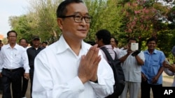 Cambodian main opposition Cambodia National Rescue Party leader Sam Rainsy, front, greets his supporters as he arrives at Choeung Ek memorial on the outskirts of Phnom Penh, Cambodia, Friday, May 17, 2015.