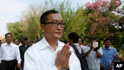 Cambodian main opposition Cambodia National Rescue Party leader Sam Rainsy, front, greets his supporters as his arrives at Choeung Ek memorial on the outskirts of Phnom Penh, Cambodia, Friday, May 17, 2015.