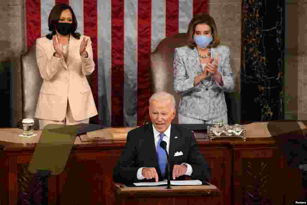 U.S. Vice president Kamala Harris and Speaker of the House Nancy Pelosi applaud as President Joe Biden addresses to a joint session of Congress in the House chamber of the U.S. Capitol in Washington, April 28, 2021.