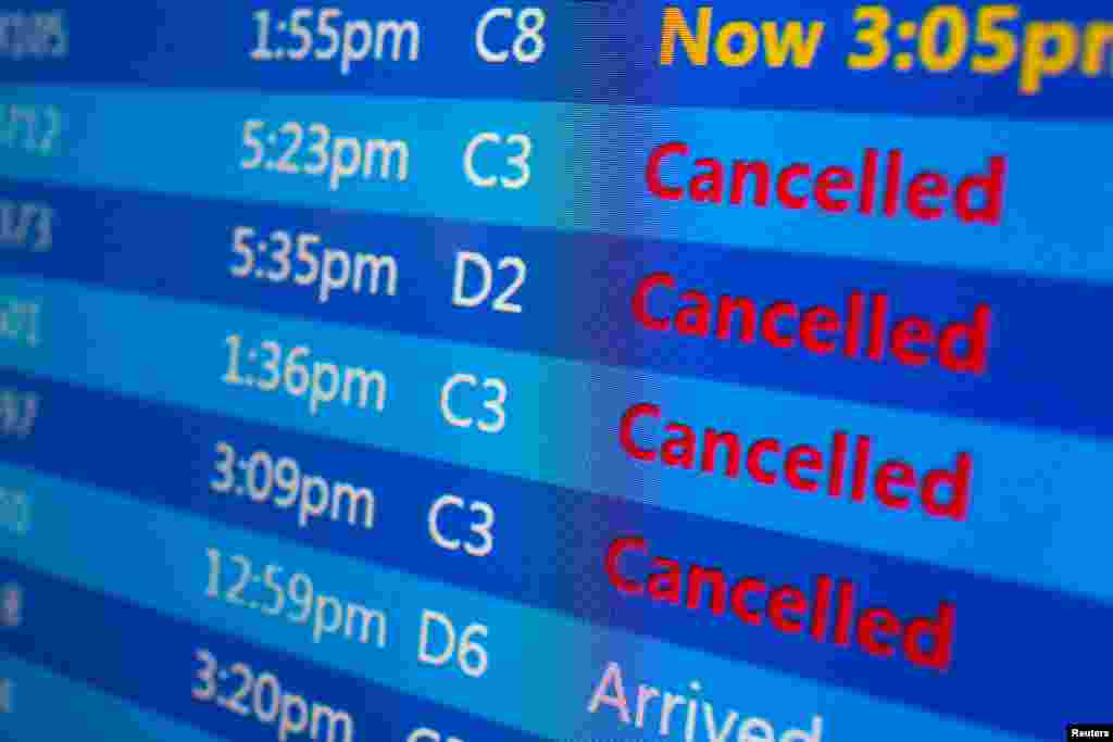 Cancelled flights are displayed on a status board at New York's Laguardia Airport ahead of a powerful approaching winter storm, Jan. 22, 2016.