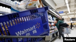 FILE - A shopping cart full of products is seen as a customer shops at a Wal-Mart store in Beijing.