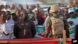 A Nigerian soldier (r) provides security as Nigerian President Goodluck Jonathan, not pictured, speaks to supporters in Yola, Nigeria, Jan. 29, 2015.