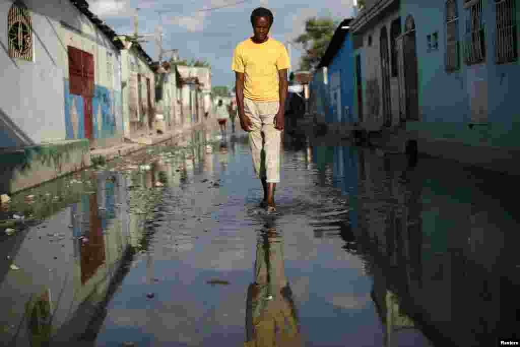 បុរសម្នាក់កំពុងដើរនៅលើផ្លូវដែលជន់លិចក្នុងនៅតំបន់Cite Soleil រដ្ឋធានីព័រអូប្រាំង (Port-au-Prince) ប្រទេសហៃទី។