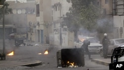 Riot police fire tear gas toward anti-government demonstrators in Musalla, Bahrain, on the edge of the capital of Manama, February 16, 2012.