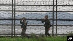 Dua tentara Korea Selatan melakukan patroli di pagar kawat berduri dekat Zona Demiliterisasi di Paju, Korea Selatan (foto: ilustrasi). Presiden Trump mempertimbangkan kemungkinan meninjau Zona Demiliterisasi Korea dalam lawatan ke lima negara Asia.