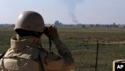 2018 yılına ait bu fotoğrafta Iraklı bir asker, dürbünle, Amerika'nın Irak-Suriye sınırına düzenlediği hava saldırısı sonrasında dumanların yükseldiği bölgeyi inceliyor.