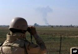 지난해 11월 이라크 국경지대인 큄에서 이라크 군인이 미군주도연합군이 ISIS를 상대로 공습하는 장면을 지켜보고 있다. (자료사진)
