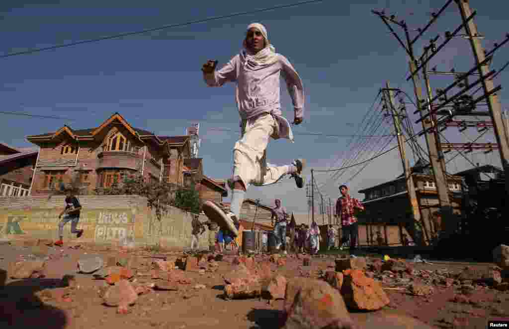 Kashmiris run for cover as Indian security forces (not pictured) fire tear gas shells during clashes, after scrapping of the special constitutional status for Kashmir by the Indian government, in Srinagar.