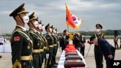 Dubes China untuk Korsel Xing Haining (kanan) memberi hormat di hadapan peti-peti yang berisi sisa jenazah tentara China, saat upacara serah terima di bandara Internasonal Incheon, Korea Selatan, 2 September 2021. (AP Photo/Ahn Young-joon, Pool)