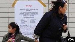 Una mujer pasa con su hija frente a una advertencia contra el virus H1N1 en un hospital de Londres.