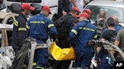 Petugas pemadam kebakaran mengangkat jenazah korban kebakaran hutan di Mati kawasan timur Athena, Selasa, 24 Juli 2018. Yunani memberlakukan masa berkabung tiga hari menyusul bencana yang menewaskan sedikitnya 74 orang tersebut.