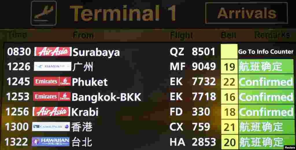Papan informasi penerbangan menunjukkan status AirAsia QZ 8501 dari kota Surabaya, Indonesia ke Singapur di Bandara Changi di Singapur, 28 Desember 2014.
