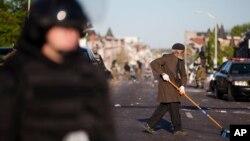 Un residente ayuda a limpiar las calles de Baltimore, luego de los pillajes del lunes por la noche.