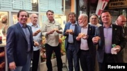 Brazil's President Jair Bolsonaro, 3rd left, eats pizza with other politicians on a street ahead of the United Nations General Assembly in New York City, September 19, 2021. (Instagram/@gilsonmachadoneto via Reuters)