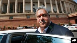 FILE - Indian business tycoon Vijay Mallya gets into his car outside the Parliament in New Delhi, India, Feb. 27, 2013.