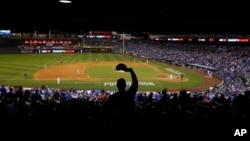 A Kansas City Royals fan cheers during the third inning of Game 3 of the American League baseball championship series.
