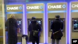 FILE - Customers uses ATM's at at a branch of Chase Bank.