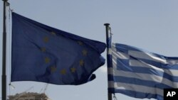 European Union flag, left, alongside Greek flag, Parthenon temple in Athens, April 11, 2011 (file photo).