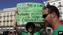Teachers hold banners and shout slogans during their protest in central Madrid. Secondary school teachers in regions around Spain began on Tuesday a strike against spending cuts they say the government is imposing as the country fights to avoid being drag