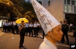 资料照片:在中国文革爆发50周年的第二天,一名抗议者在通往香港政府总部的路上戴着文革时期被批斗者的高帽,反对文革政治,另一位抗议者打着黄雨伞,象征对真普选的诉求。(2016年5月27日)