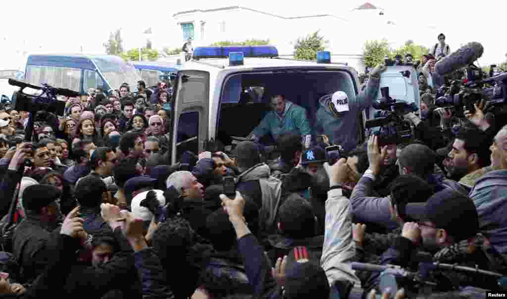 The body of Chokri Belaid, a prominent Tunisian opposition politician, is carried into an ambulance after he was shot, in Tunis Feb. 6, 2013.