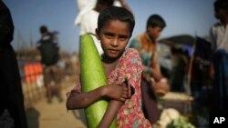 지난 21일 방글라데시 콕스바자르 인근의 난민촌에 거주하는 로힝야족 소녀가 시장에서 가져온 채소를 들고 있다.