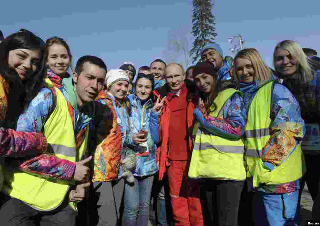 Russian President Vladimir Putin poses for a photograph with volunteers during his visit to watch the men's cross country skiing relay during the Sochi 2014 Olympic Winter Games at Laura Cross-Country Ski and Biathlon Center near Krasnaya Polyana, Russia, Feb. 16, 2014.