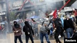 Para demonstran melemparkan batu dalam bentrokan dengan polisi saat pawai di Mexico City, 26 September 2015.