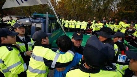 Cảnh sát ngăn chặn 1 cư dân Paju lao đến 1 chiếc xe của các nhà hoạt động chống Bắc Triều Tiên gần khu phi quân sự ngăn cách 2 miền Triều Tiên, ở Paju, ngày 25/10/2014.