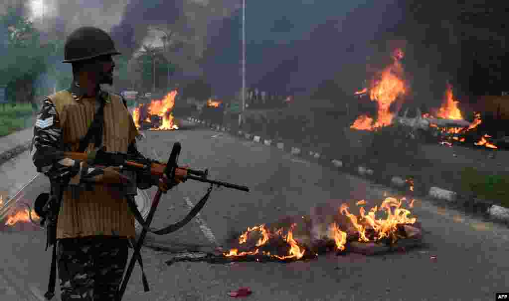 Indian security personnel looks at burning vehicles set alight by rioting followers of a religious leader convicted of rape in Panchkula.