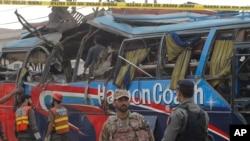 Petugas keamanan Pakistani memeriksa bis yang hancur akibat ledakan bom di Peshawar, Pakistan (16/3)