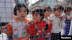 Vietnamese refugee children peek from Hong Kong's Pillar Point Refugee Centre March 9 during a visit by United Nations High Commissioner for Refugees (UNHCR) chief Sadako Ogata.