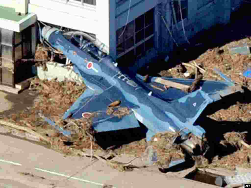 A Japan Self Defense Forces fighter jet is swept into a building by a tsunami at an airbase in Higashimatsushima City, Miyagi Prefecture in northeastern Japan March 12, 2011.