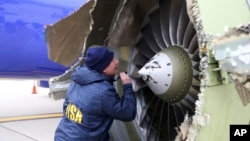 A National Transportation Safety Board investigator examines damage to the engine of the Southwest Airlines plane that made an emergency landing at Philadelphia International Airport in Philadelphia, April 17, 2018. (NTSB via AP)
