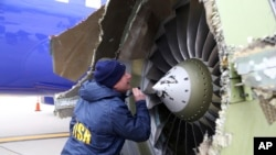A National Transportation Safety Board investigator examines damage to the engine of the Southwest Airlines plane that made an emergency landing at Philadelphia International Airport in Philadelphia, April 17, 2018.