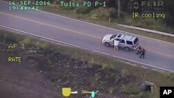 FILE - In this photo made from a Sept. 16, 2016, police video, Terence Crutcher, left, with his arms up, is pursued by police officers as he walks next to his stalled SUV moments before he was shot and killed by one of the officers in Tulsa, Okla.