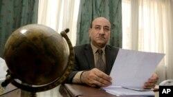 ARSIP - Hesham Genena, kepala audit Mesir, memegang dokumen di kantornya di Kairo, 16 April 2014.