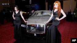 អ្នកបង្ហាញម៉ូដឈរថតក្បែររថយន្ត Rolls-Royce Wraith មួយគ្រឿងក្នុងអំឡុងពិធីសម្ពោធការបើកលក់នៅរាជធានីភ្នំពេញកាលពីថ្ងៃទី៩ ខែឧសភា ឆ្នាំ២០១៤។