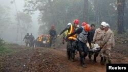 Rescatistas recuperan los cadáveres del helicóptero accidentado.