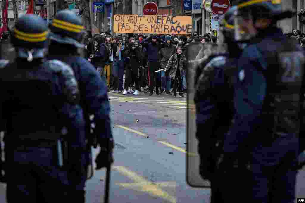 High school students demonstrate in front of riot police in Lyon, France, to protest against the different education reforms, including changes to university entrance requirements.