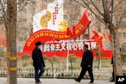 """FILE - Residents walk past government propaganda, some of which reads, """"Socialist core values,"""" in Hotan in northwestern China's Xinjiang Uyghur Autonomous Region, March 22, 2021."""