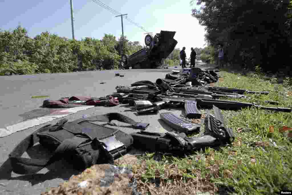 Gear and weapons of victims are placed by the road as security forces inspect the site of a bomb attack on police in the troubled southern Thai province of Narathiwat, March 30, 2014.