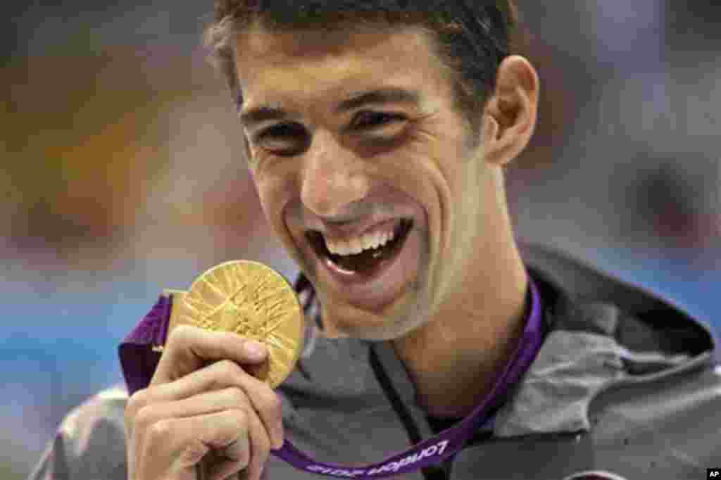 United States' Michael Phelps displays his gold medal for the men's 100-meter butterfly swimming final at the Aquatics Centre in the Olympic Park during the 2012 Summer Olympics in London, Friday, Aug. 3, 2012. (AP Photo/Matt Slocum)