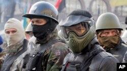 Người biểu tình chống chính phủ, trong trang phục và nón bảo hộ, chuẩn bị cho cuộc biểu tình tại Quảng trường Độc lập trong thủ đô Kyiv, Ukraina, 6/2/14