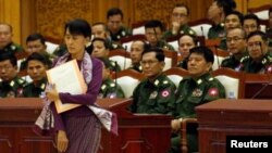 Aung San Suu Kyi walks to take her oath at the lower house of parliament in Burma.
