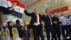 """Syrian Kurds carry a Syrian flag bearing a picture of President Bashar Assad and Arabic writing that reads: """"God protects Syria's Assad"""" as they celebrate the Nowruz spring festival with a traditional dance in Damascus, March 20, 2011"""